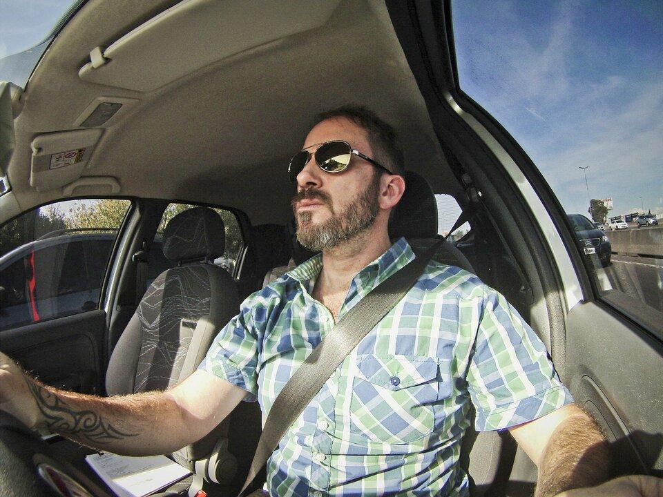 Zdjęcie przedstawia wnętrze samochodu oraz kierującego nim mężczyznę uchwycone za pomocą obiektywu szerokokątnego. Aparat umieszczony po lewej stronie kierownicy objął swoim polem widzenia całe wnętrz kabiny tworząc obraz ocharakterystycznych okrągłych zniekształceniach wzdłuż krawędzi kadru. Kierowca wcentralnej części zdjęcia ma krótkie włosy, brodę, okulary lustrzanki ijasną kraciastą koszulę zkrótkimi rękawami. Jest skupiony na drodze iprzypięty do fotela pasem bezpieczeństwa. Na zewnątrz samochodu ruch uliczny imijające go samochody na drodze kilkupasmowej.