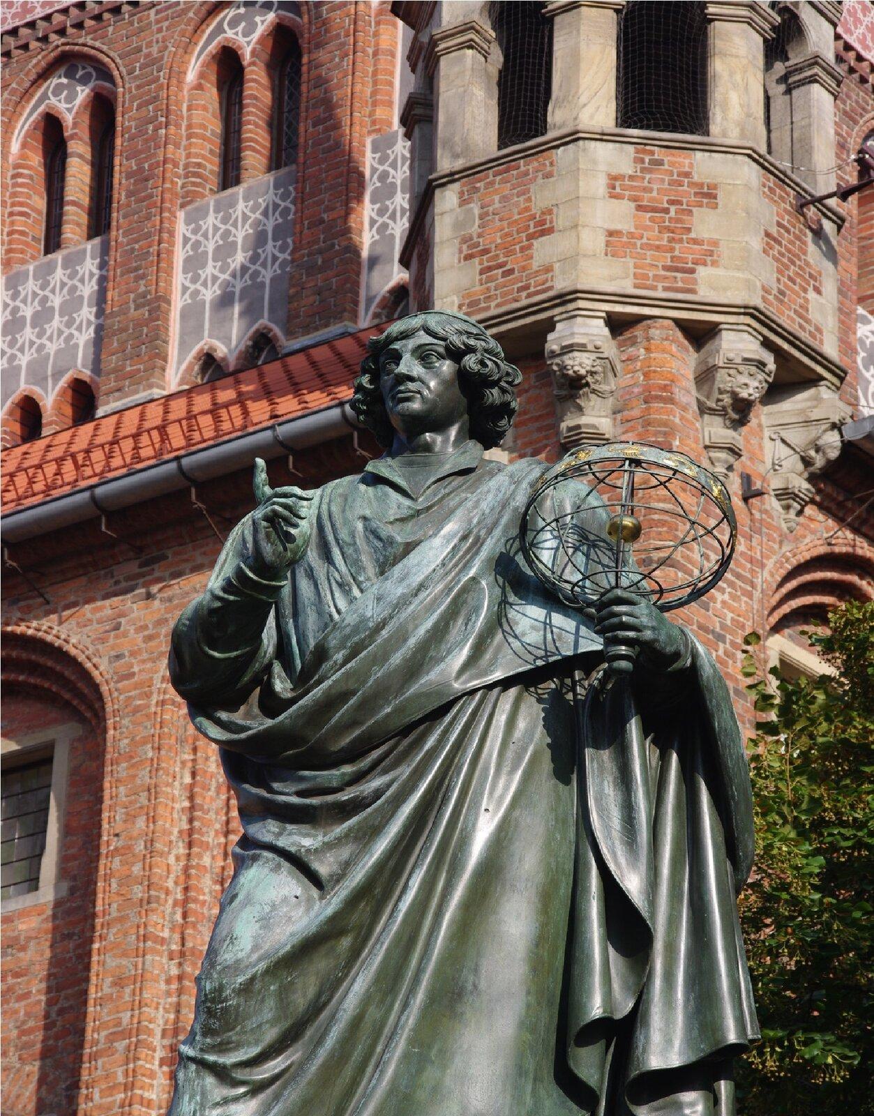 Ilustracja przedstawia posąg Mikołaja Kopernika wToruniu. Rzeźba ukazuje stojącego mężczyznę wśrednim wieku zpółdługimi, falowanymi włosami. Postać okryta jest pofałdowaną peleryną. Wlewej dłoni trzyma ażurowy model układu słonecznego. Prawą rękę zwysuniętym do góry, wskazującym palcem ma zgiętą włokciu ilekko uniesioną. Odlana zbrązu, ciemno-zielona rzeźba ustawiona jest na tle wykonanej zczerwonej cegły, barokowej fasady.