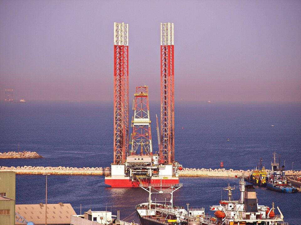 Na zdjęciu zabudowania portowe, wysokie rusztowania, kilka statków.