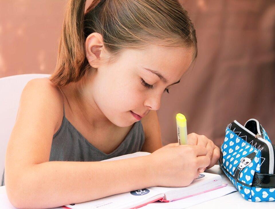 Fotografia przedstawia dziewczynkę siedzącą na krześle przy stole, zapisującą wkalendarzu plan dnia.