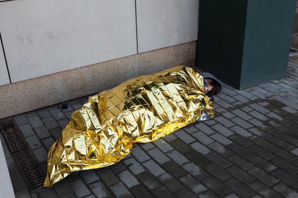 Kolorowe zdjęcie przedstawia osobę śpiącą na chodniku. Dzień. Osoba bokiem do obserwatora. Śpiąca osoba okryta jest złotym kocem ratunkowym. Po prawej strony głowa wkapturze. Jedynie głowa nie jest przykryta folią. Za plecami osoby śpiącej betonowa ściana budynku.