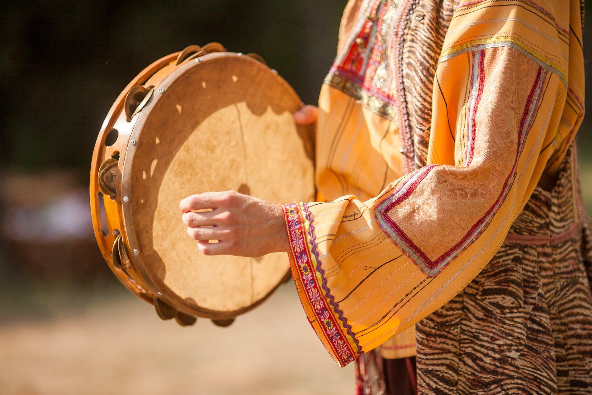Ilustracja przedstawia tamburyn znany także jako bębenek baskijski. Na zdjęciu jest on trzymany przez kobietę wkolorowym stroju ludowym.