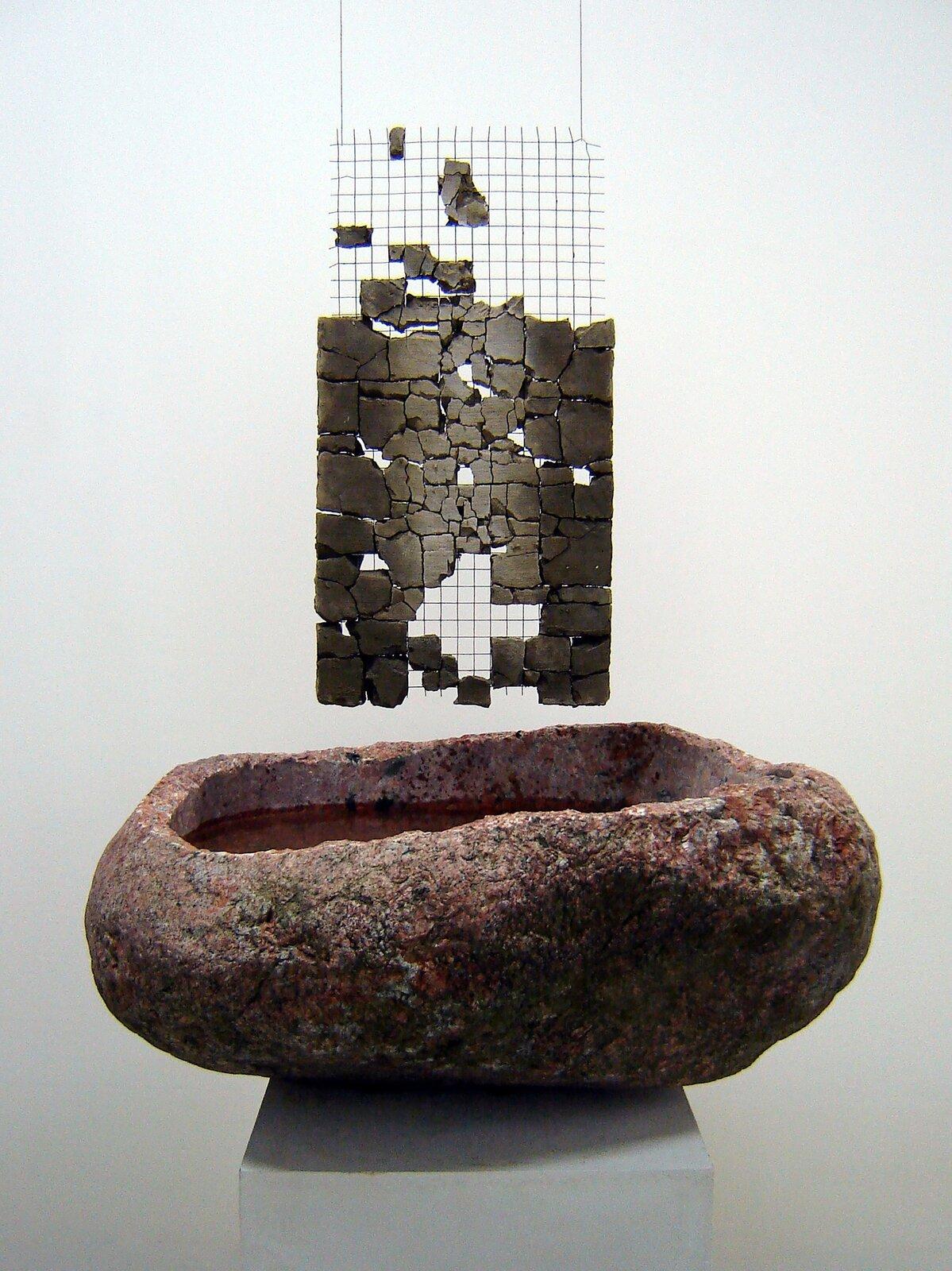 """Ilustracja przedstawia rzeźbę """"Źródło IV"""" autorstwa Macieja Wierzbickiego. Na zdjęciu ukazany jest nieregularny, czerwonawy, szorstki kamień zgranitu oobłym kształcie, wktórego wyżłobionym wnętrzu znajduje się woda. Nad jej taflą zwisa prostokątna, stalowa siatka zumieszczoną na niej płaszczyzną pokruszonej, szarej gliny. Obiekt ustawiony jest na jasno-szarym, sześciennym postumencie. Tło stanowi biała przestrzeń."""