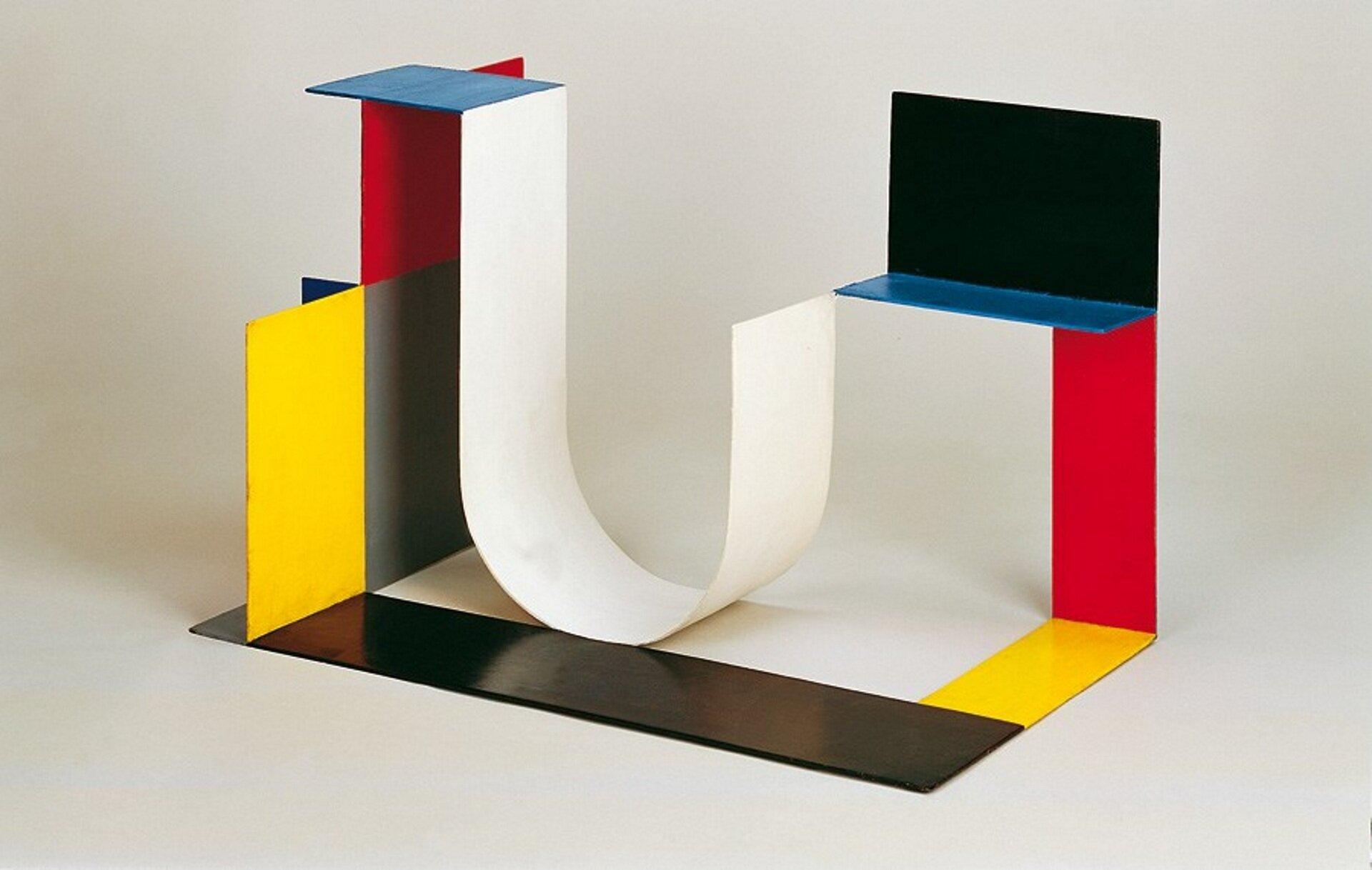 """Ilustracja przedstawia abstrakcyjną rzeźbę zmetalu autorstwa Katarzyny Kobro pt. """"Kompozycja przestrzenna 4"""". Kompozycja składa się zprostokątnych fragmentów wróżnych kolorach ioróżnej wielkości połączonych między sobą jedną krawędzią. Prostokąty są wkolorach żółtym, czarnym, czerwonym iniebieskim. Wcentralnej części jest jeden fragment który został wygięty wkształcie odwróconej litery j. Jest wkolorze białym."""