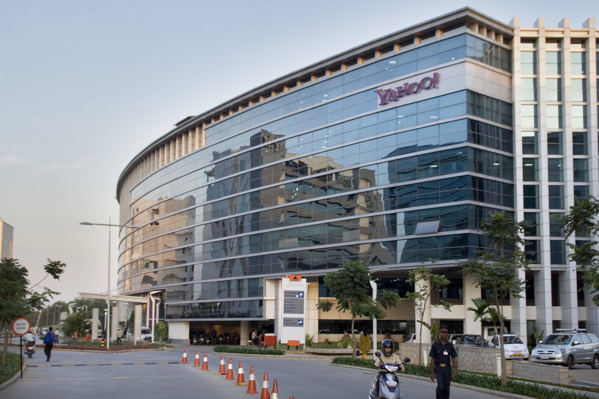 Na zdjęciu nowoczesny dziesięciopiętrowy budynek biurowy. Duże powierzchnie szklane. Napis Yahoo! Przed budynkiem droga dojazdowa na parking, kilka słupków drogowych, drzewa. Przechodnie.