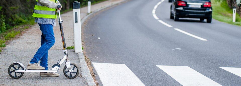 Kolorowe zdjęcie przedstawiające jezdnię znamalowanymi na niej pasami dla pieszych. Prawą stroną jezdni jedzie samochód, widoczny jest tylko jego odjeżdżający tył zczerwonymi światłami. Na chodniku, po lewej stronie jezdni, stoi dziecko zhulajnogą, widoczne od ramion wdół. Prawa noga oparta na hulajnodze. Dziecko ma założoną kamizelkę odblaskową.