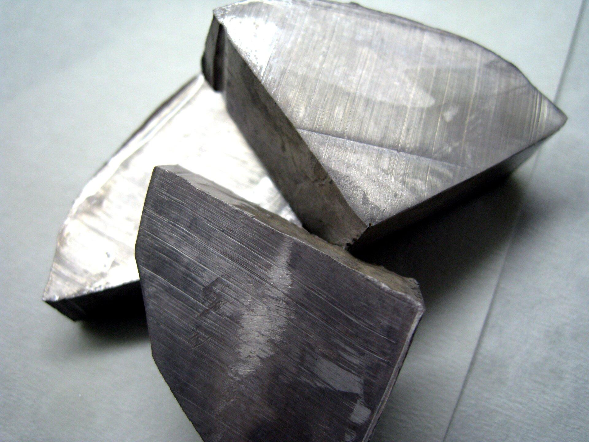 Zdjęcie przedstawia nieregularne kawałki srebrnego metalu orównych, gładkich krawędziach.