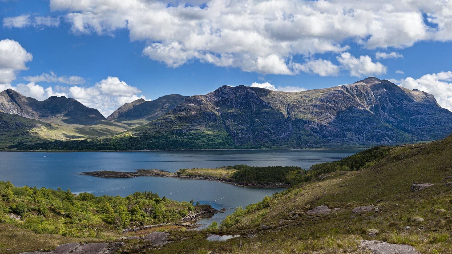 Na zdjęciu pasmo górskie, stoki skaliste, szczyty płaskie, wdolinie na pierwszym plnie zbiornik wodny.