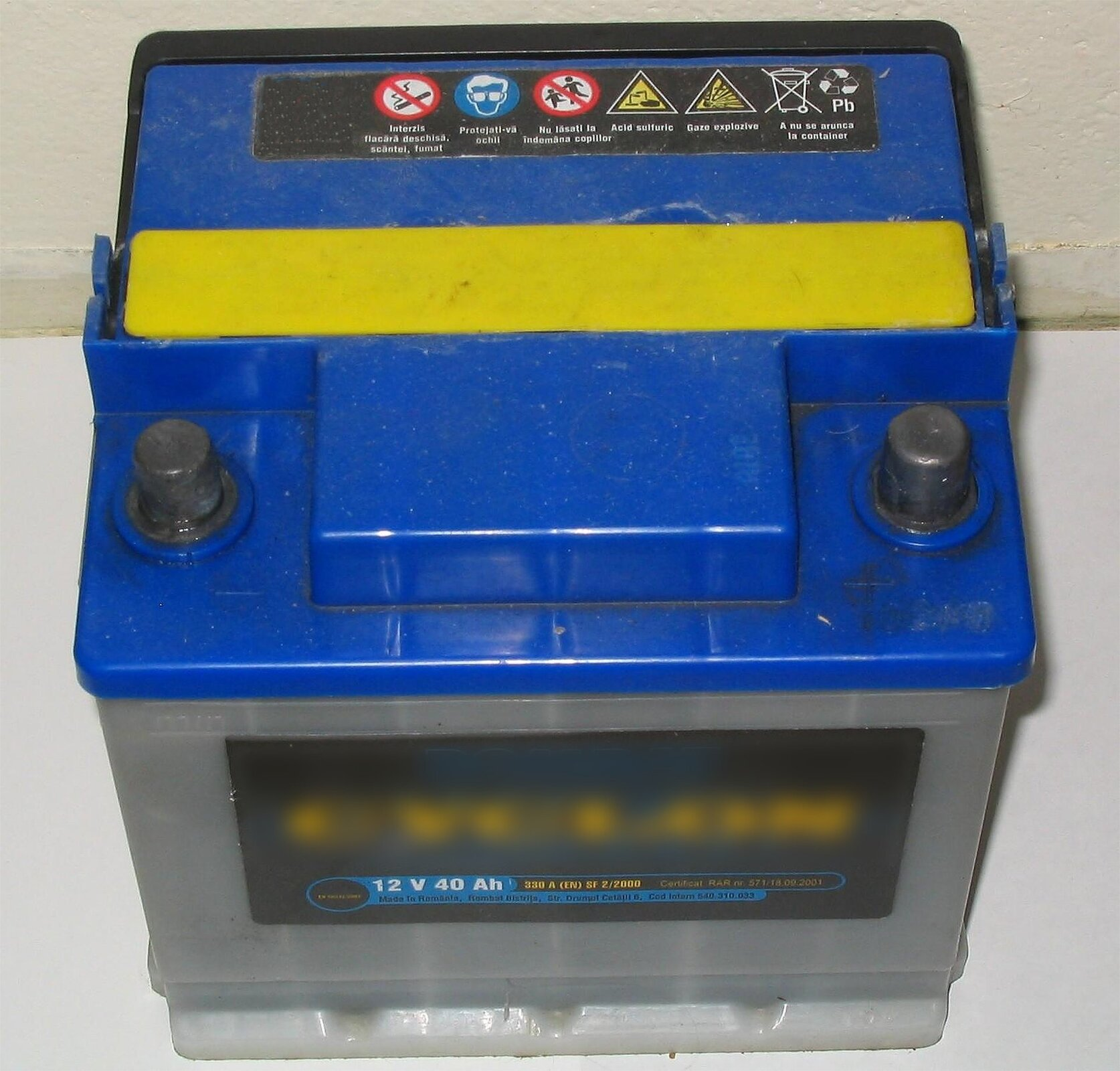 Zdjęcie przedstawia samochodowy akumulator ołowiowy pokazany zprzodu izgóry. Obudowa szara, pokrywa niebieska zżółtą rączką. Dwie grube metalowe elektrody po prawej ilewej stronie. Na etykiecie zprzodu nazwa marki iparametry: napięcie 12 woltów, pojemność 40 amperogodzin.