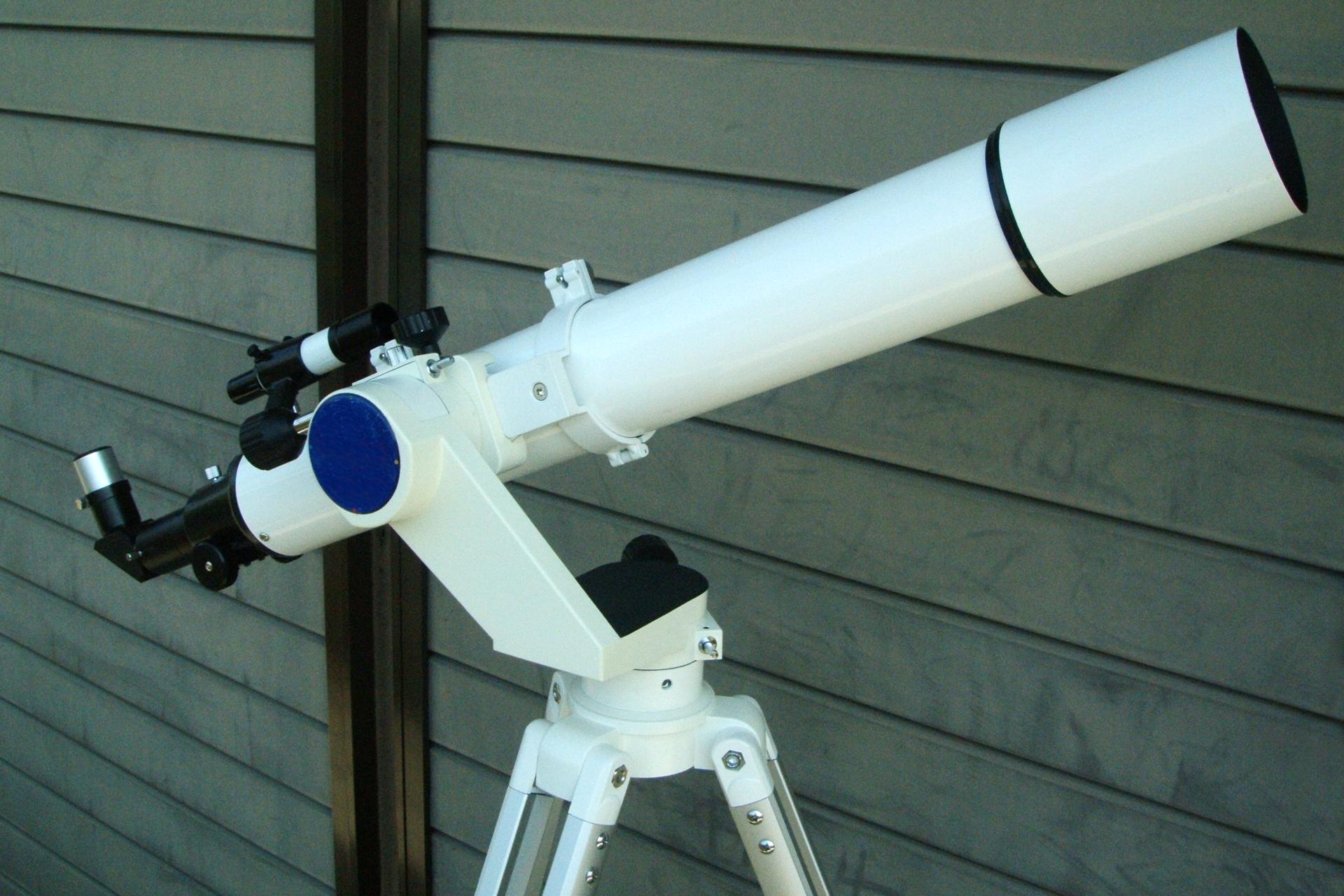 Fotografia prezentuje teleskop na statywie wbiałej obudowie.