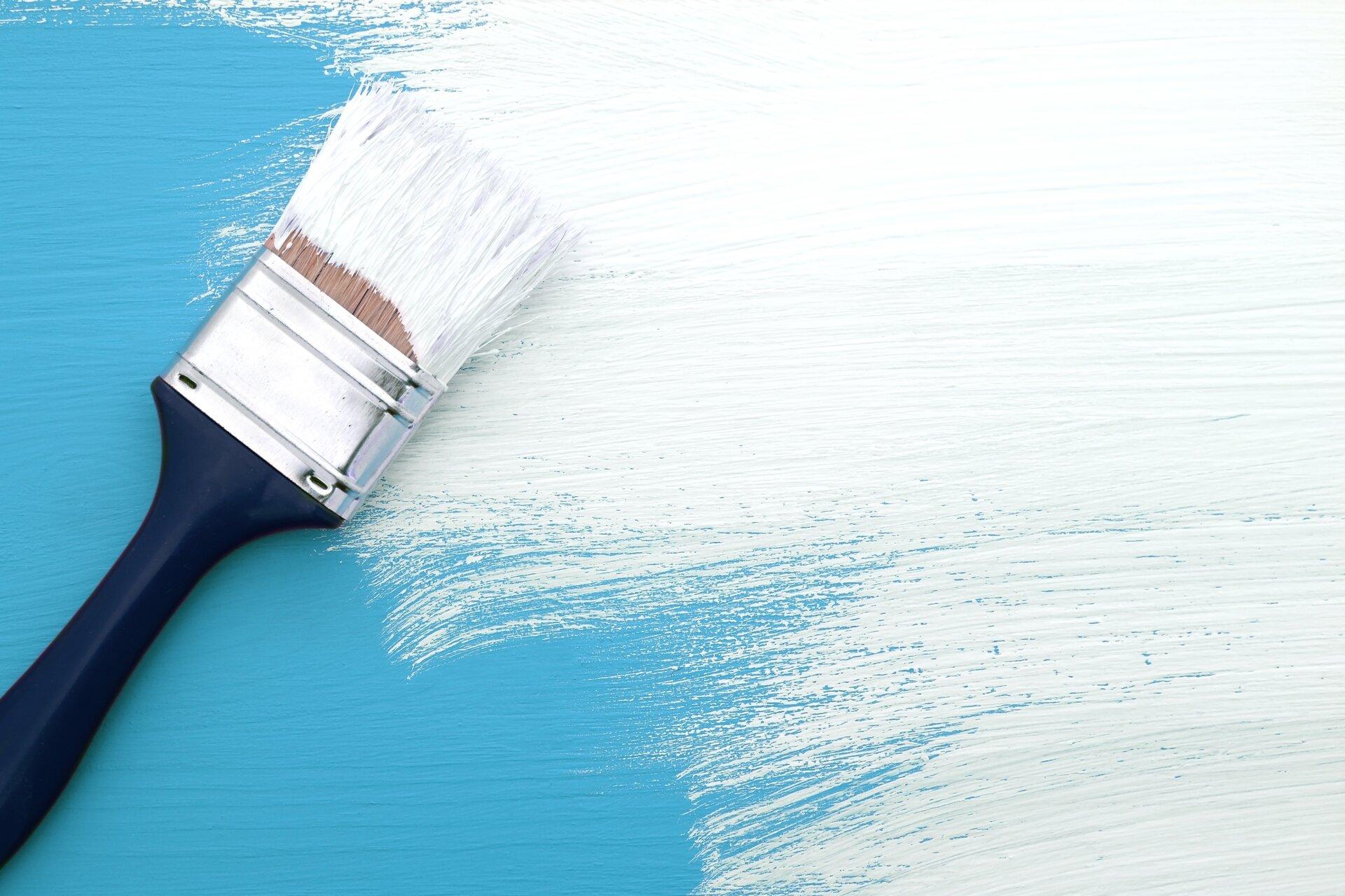 Ilustracja jest zdjęciem przedstawiającym niebieską deskę, częściowo zamalowaną pędzlem na biało. Po lewej stronie znajduje się zamoczony wfarbie szeroki pędzel.
