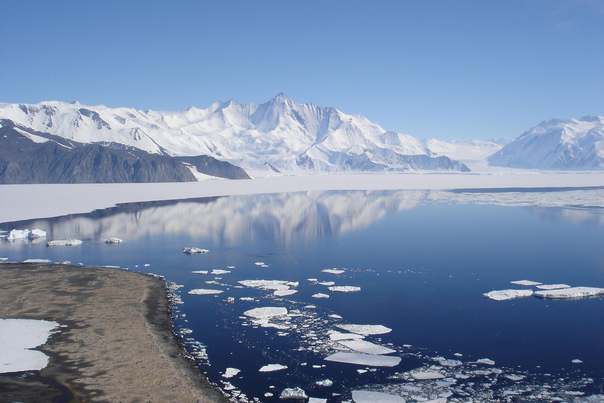 Galeria fotografii prezentujących krajobrazy wróżnych strefach oświetlenia Ziemi. Fotografia pierwsza prezentuje ośnieżone góry nad wodą wstrefie podbiegunowej.