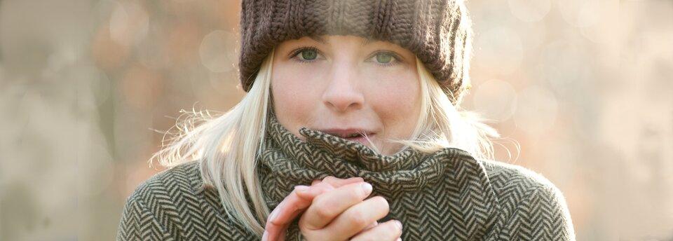 Kolorowe zdjęcie przedstawia młodą kobietę zjasnymi włosami do ramion, ubraną wpłaszcz wbiało-czarne ukośne wzory iwbrązową ciepłą czapkę. Kobieta ma splecione dłonie, trzyma je blisko twarzy, jest jej zimno. Ma zaczerwienione od mrozu policzki.