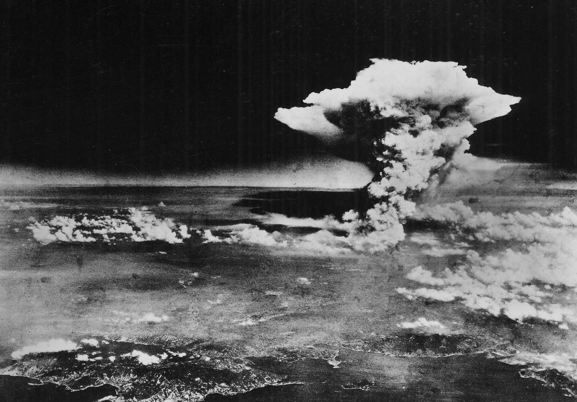 Czarno-białe zdjęcie nr 2 przedstawia chmurę atomową nad Hiroszimą. Chmura pyłów wznosi się wysoko nad powierzchnię Ziemi. Szare uniesione pyły tworzą chmurzę wkształcie grzyba. Pionowa noga grzyba rozszerza się ku górze tworząc kopułę.