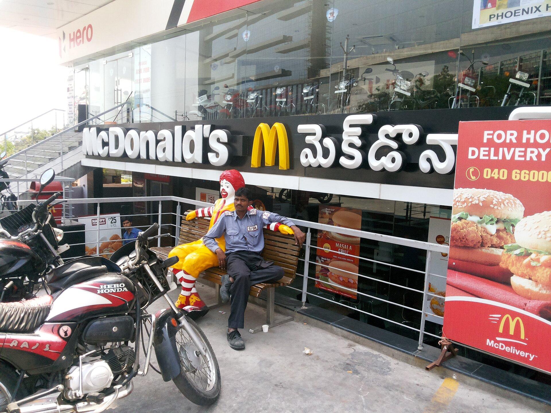 Na zdjęciu restauracja wIndiach. Przed restauracją na ławce siedzi mężczyzna ociemnej karnacji – Hindus. Obok niego plastikowa maskotka restauracji – klaun naturalnych rozmiarów człowieka. Przed restauracją zaparkowane motocykle.