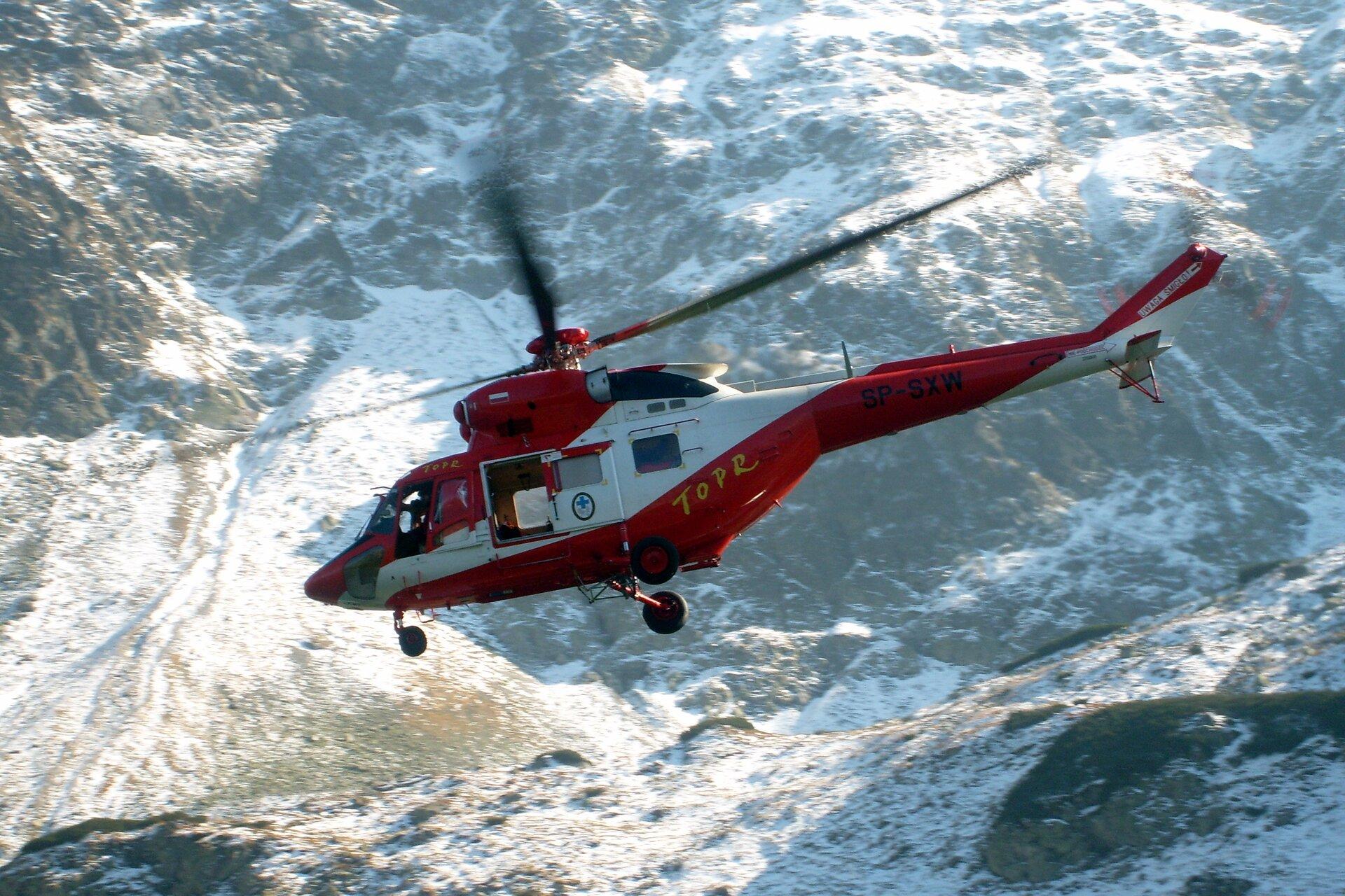 Zdjęcie przedstawia helikopter TOPR wtrakcie akcji ratunkowej. Na pierwszym planie, na środku kadru białoczerwony helikopter lecący na tle górskich zboczy oświetlonych słońcem ipokrytych częściowo śniegiem. Lewy bok helikoptera zwrócony do obserwatora zdjęcia, ogon helikoptera po prawej stronie, awięc helikopter leci wlewo. Kadłub helikoptera wkolorze czerwonym zukośnym białym pasem. Właz boczny otwarty, na drzwiach owalny znak służb górskich zniebieskim krzyżem wśrodku. Na kadłubie po prawej stronie napis TOPR, wykonany dużymi żółtymi literami.