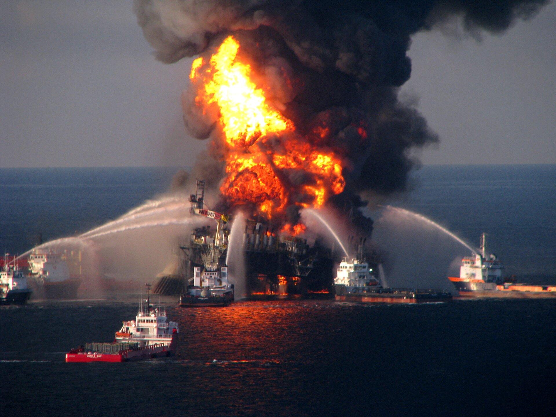 Na zdjęciu płonąca platforma wiertnicza. Czerwono-żółty ogień, kłęby szarego dymu. Dookoła platformy na wodzie pięć statków, zktórych wkierunku platformy lecą silne strumienie wody.