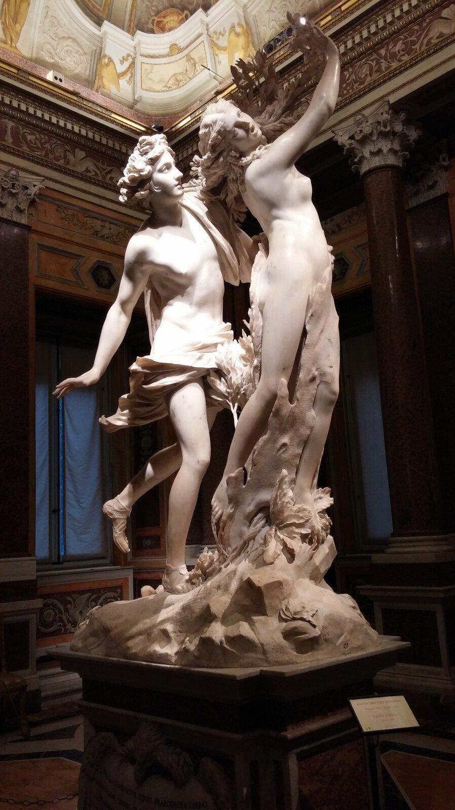"""Fotografia przedstawia rzeźbę Gian Lorenzo Berninego pt. """"Apollo iDafne zmieniająca się wdrzewo laurowe"""". Figura składa się zdwóch części – podobizny Apolla iDafne, która przeistacza się wdrzewo. Apollo to młody szczupły mężczyzna, który ma średniej długości kręcone włosy, jest przepasany chustą, która zakrywa jego genitalia, na jego nogach widoczne są sandały. Mężczyzna zzaciekawieniem obserwuje kobietę, która zamienia się wdrzewo. Dafne to naga imłoda kobieta, odługich włosach. Kobieta jest wtrakcie transformacji – jej nogi zamieniają się wkorę drzewną, aręce zamieniają się wliściaste gałęzie. Kobieta jest przerażona, na jej twarzy widoczny jest ból icierpienie. Figura Apolla iDafne została wykonana zjasnego kamienia, iznajduje się wSali wystawowej."""