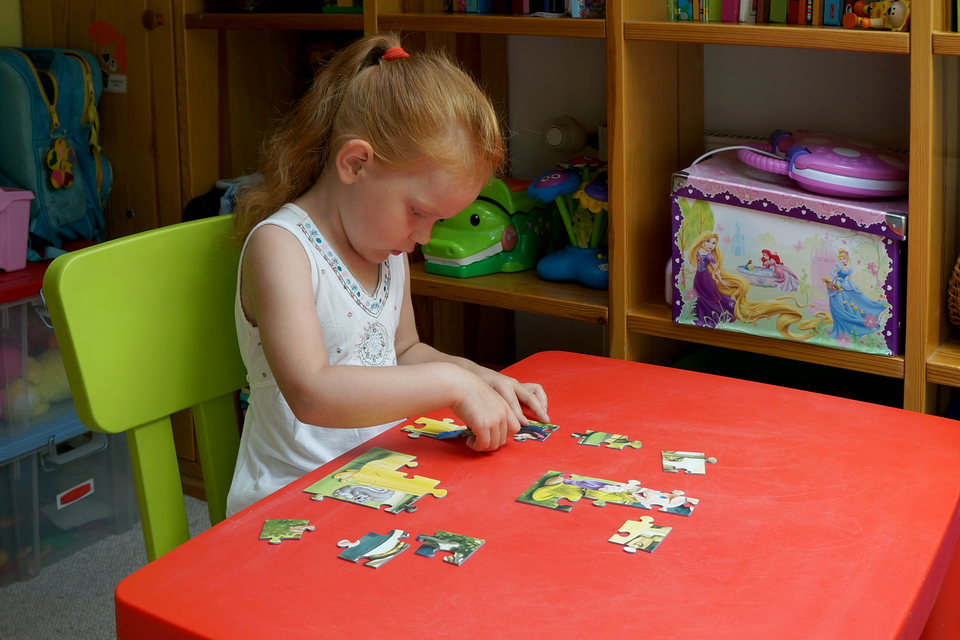 Fotografia przedstawia dziecko wwieku około czterech lat. Dziewczynka siedzi przy stole, samodzielnie układa puzzle. Rozwija zdolność logicznego myślenia.