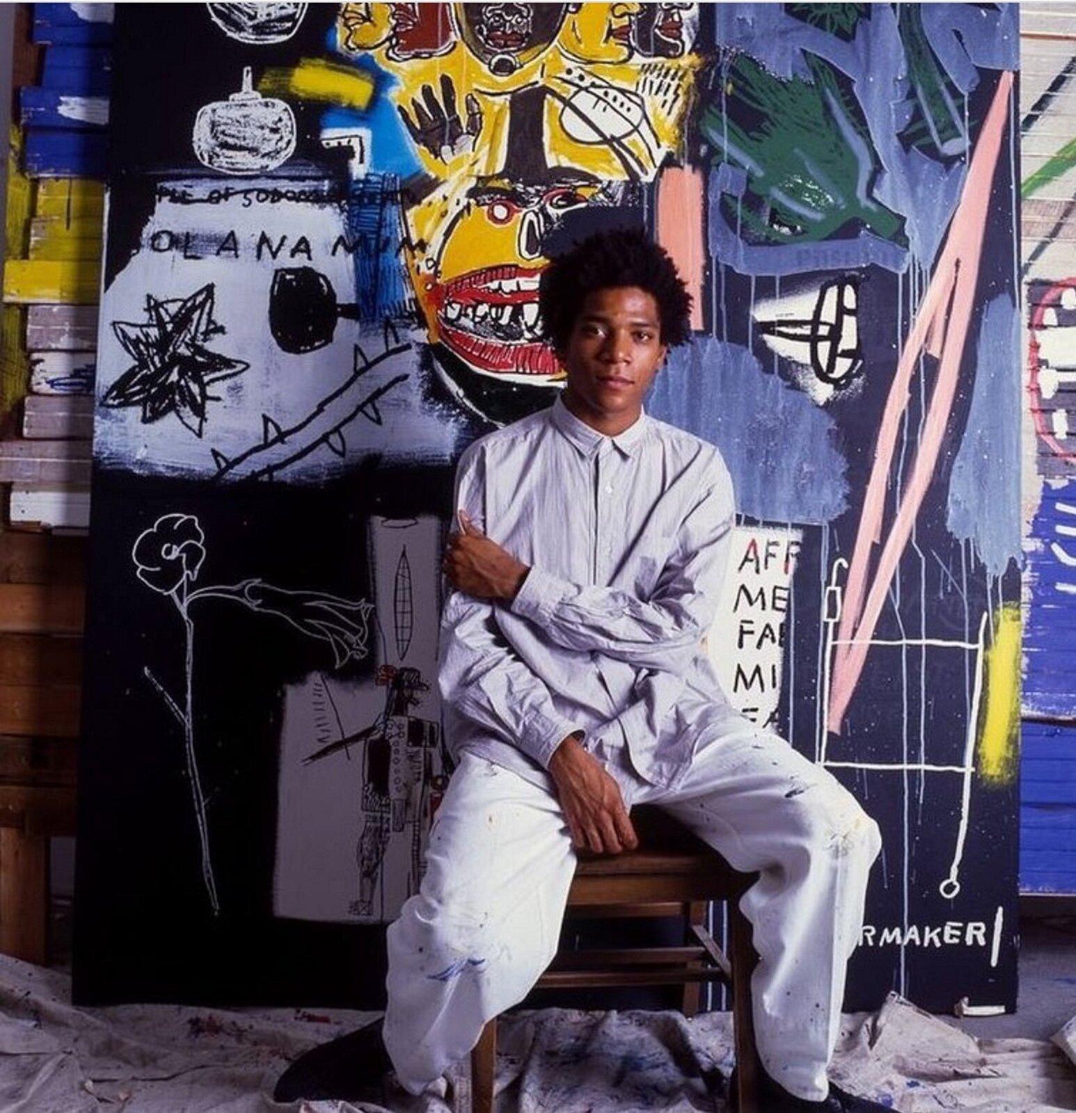 Ilustracja przedstawia zdjęcie Jeana Michela Basquiata na tle jego prac. Czarnoskóry mężczyzna ma czarne, kręcone włosy iubrany jest wbiałą koszulę ispodnie. Siedzi na drewnianym krześle. Lewą rękę trzyma na prawym przedramieniu,. Prace wtle są bardzo ekspresyjne, malowane intensywnymi barwami iprzypominają dziecięce rysunki.