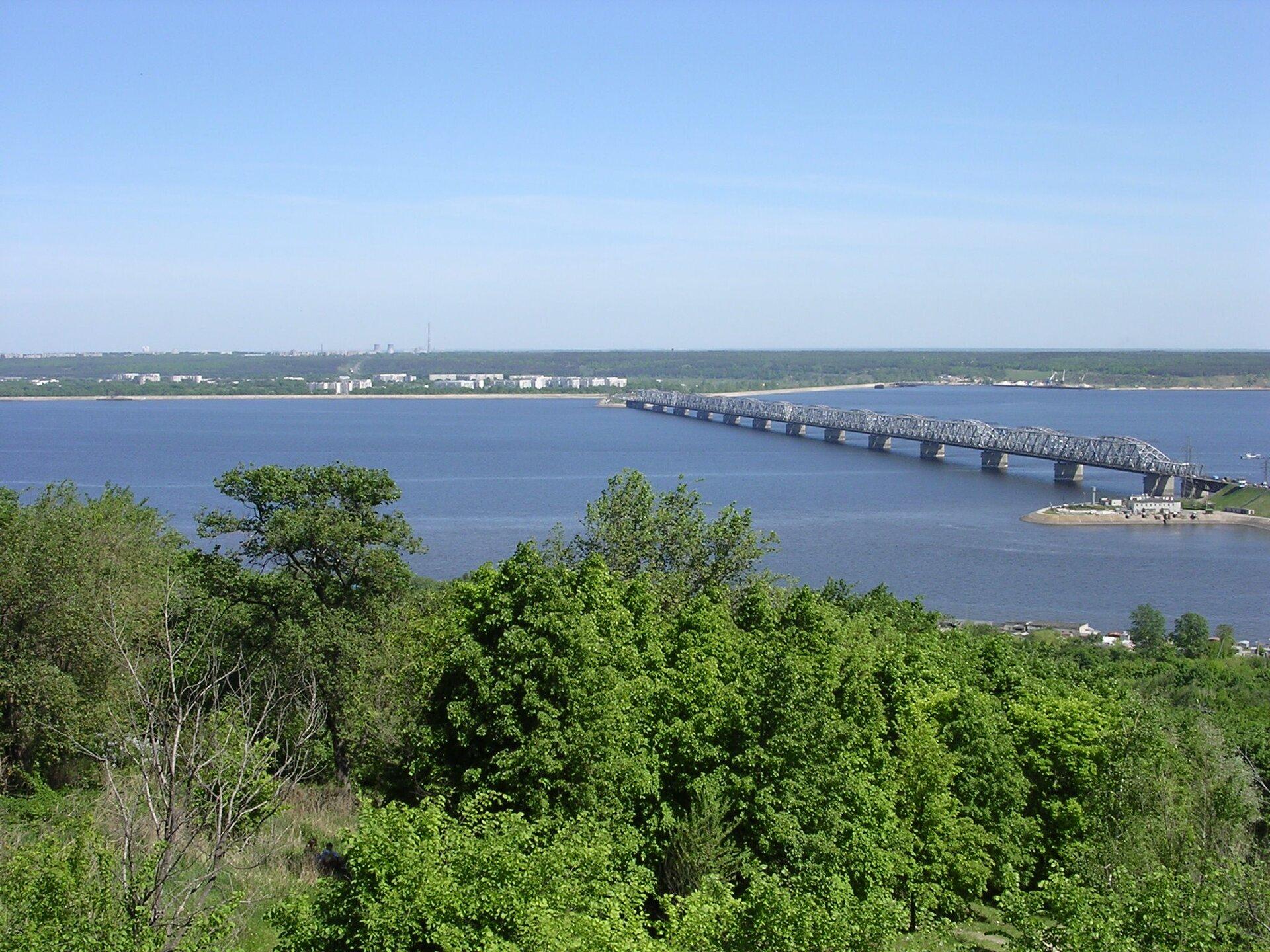 Na zdjęciu szeroka rzeka, na bliższym brzegu las liściasty, na drugim brzegu zabudowania, wtle zakład przemysłowy, kominy. Zprawej strony most.