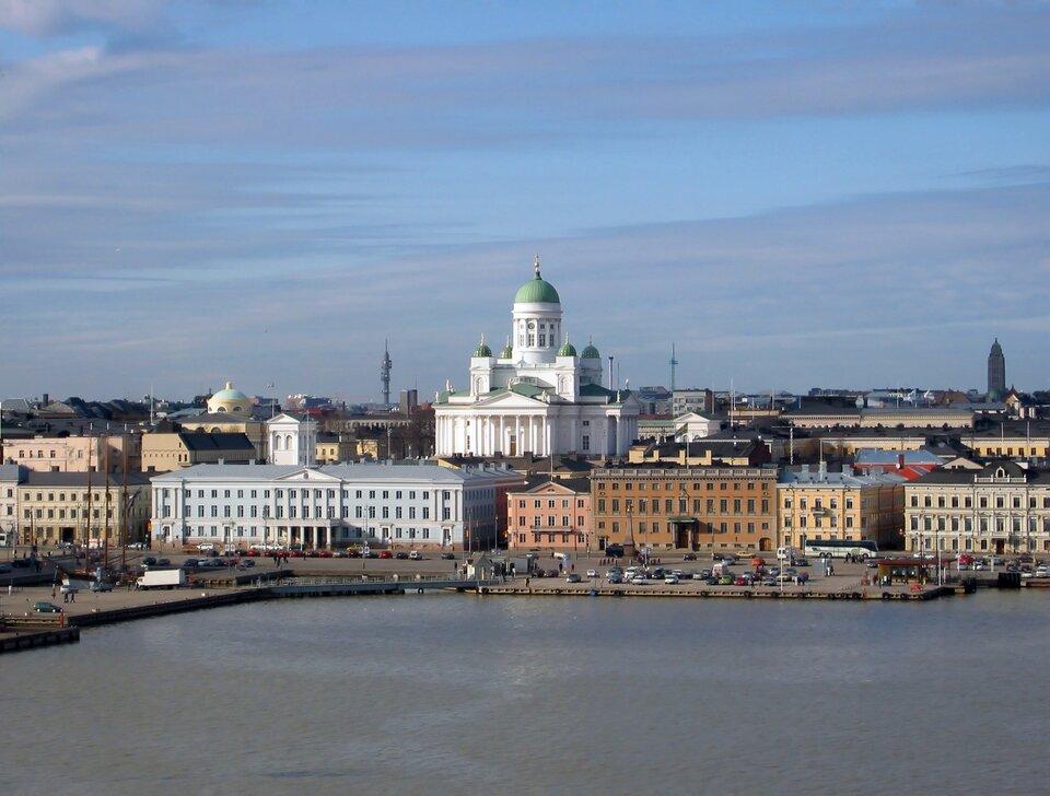 Na zdjęciu zwarta zabudowa miejska nad brzegiem zbiornika wodnego. Betonowy brzeg. Wcentrum bardzo wysoki biały budynek katedry, pięć zielonych kopuł.