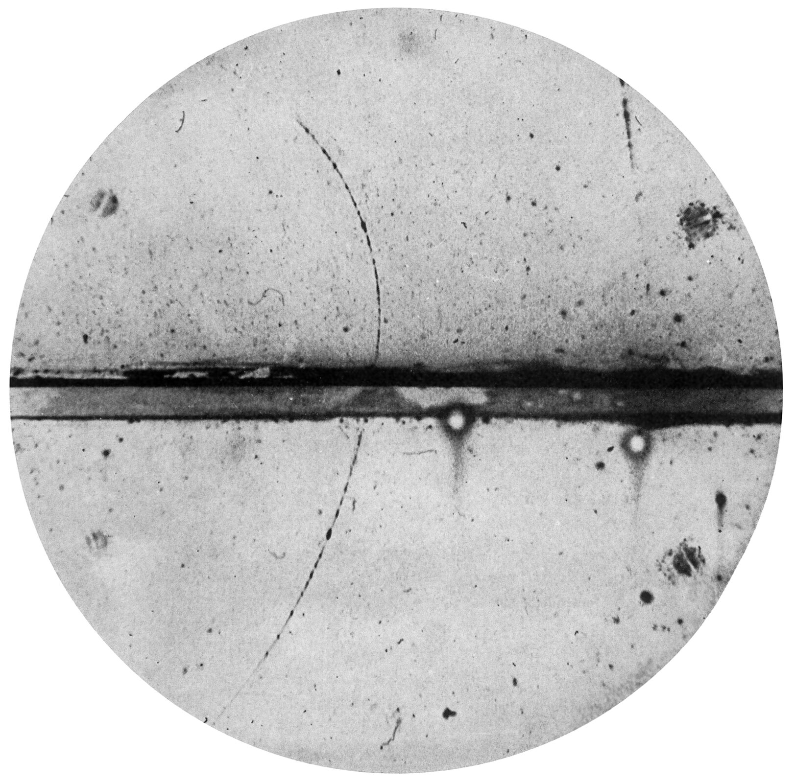Ilustracja przedstawia tory naładowanych cząsteczek zarejestrowane wkomorze Wilsona. Fragment ma kształt koła. Wnętrze jasnoszare, zwidocznymi czarnymi małymi plamkami, nieregularnie rozłożonymi. Przez środek przebiega ciemnoszare, miejscami prawie czarne, poziome, proste wgłębienie.