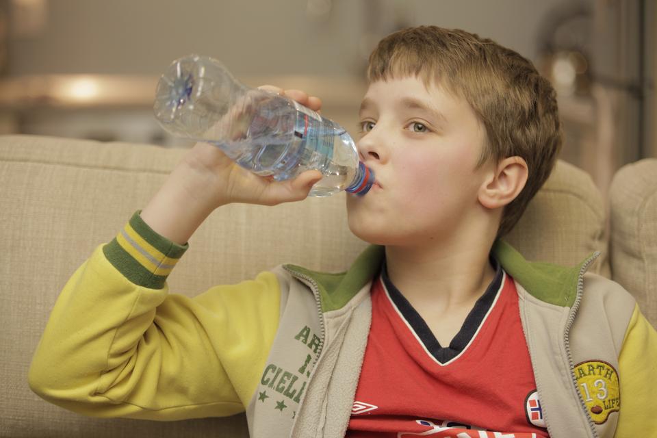 Fotografia przedstawiająca chłopca pijącego wodę zbutelki