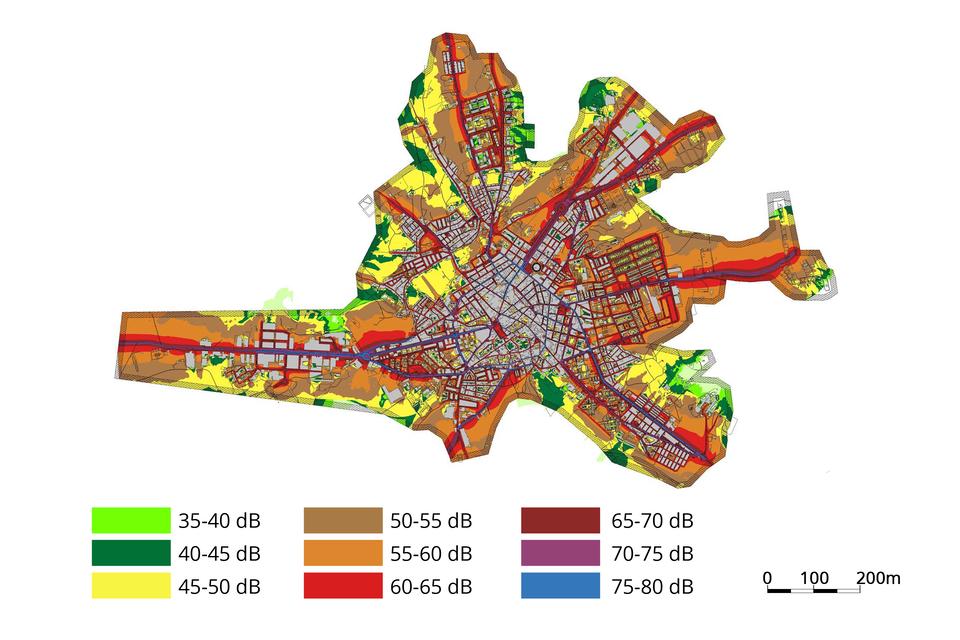 Fotografia przedstawia fragment planu miasta. Pod nim podziałka ikolorowa skala natężenia dźwięku wdecybelach. Na planie miasta naniesiono barwy skali. Wysokie natężenie hałasu zaznaczono na przykład przy ciągach komunikacyjnych. Powstała mapa akustyczna miasta.