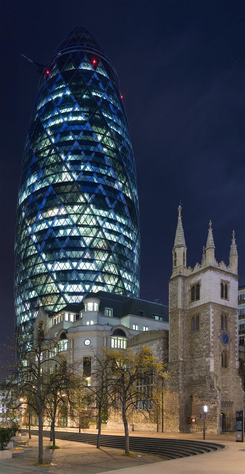 Zdjęcie przedstawia przypominający kształtem wielki pocisk wieżowiec 30 Saint May Axe. Budowla ma 180 metrów wysokości ijest pokryta podwójną szklaną elewacją. Na zdjęciu przedstawiony jest nocą zefektownym oświetleniem iklasycznymi londyńskimi budynkami na pierwszym planie.