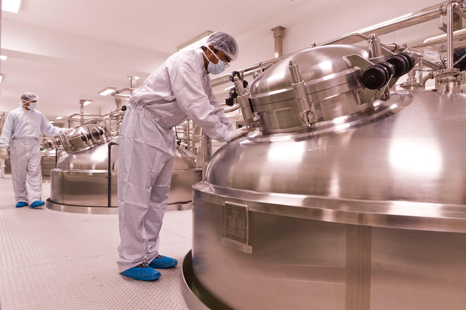 Fotografia przedstawia wnętrze zakładu, produkującego insulinę przy pomocy bakterii. Stoją olbrzymie metalowe kadzie, wktórych hoduje się odpowiednio zmodyfikowane mikroorganizmy. Przy kadziach ludzie wbiałych kombinezonach, ochraniaczach na buty, rękawiczkach imaseczkach.