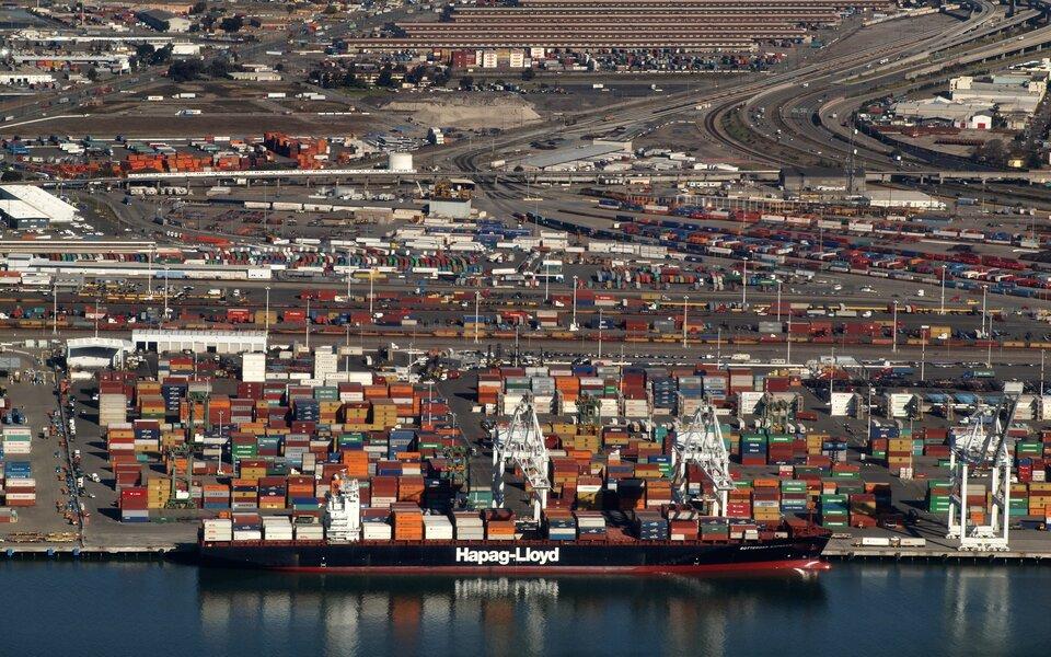 Na zdjęciu na pierwszym planie statek kontenerowiec pełen kolorowych kontenerów. Wtle port. Duża ilość kontenerów. Drogi dojazdowe, latarnie.