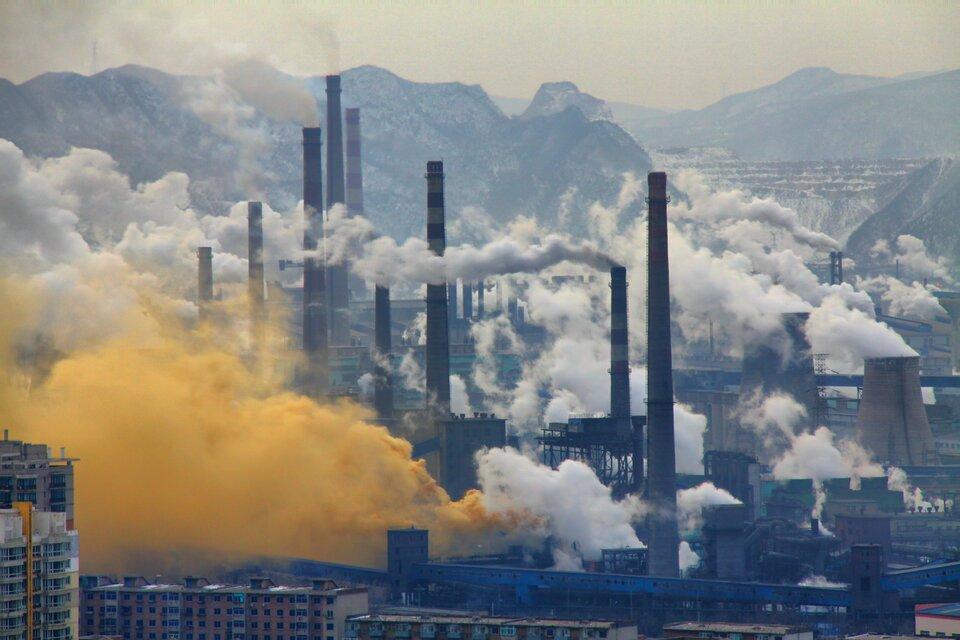 Na zdjęciu teren przemysłowy. Duża liczba wysokich, dymiących kominów. Dym ma różne kolory: żółty, szary, biały. Dym jest bardzo gęsty. Na drugim planie wysokie góry.