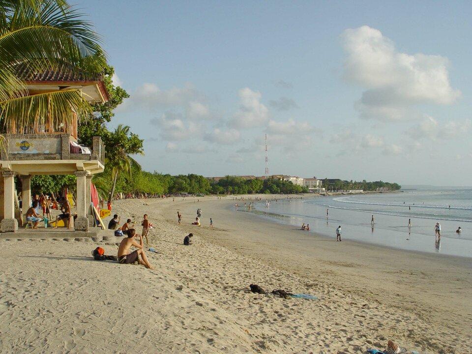 Na zdjęciu plaża nad morzem. Na brzegu palmy. Wtle zabudowania hotelowe.