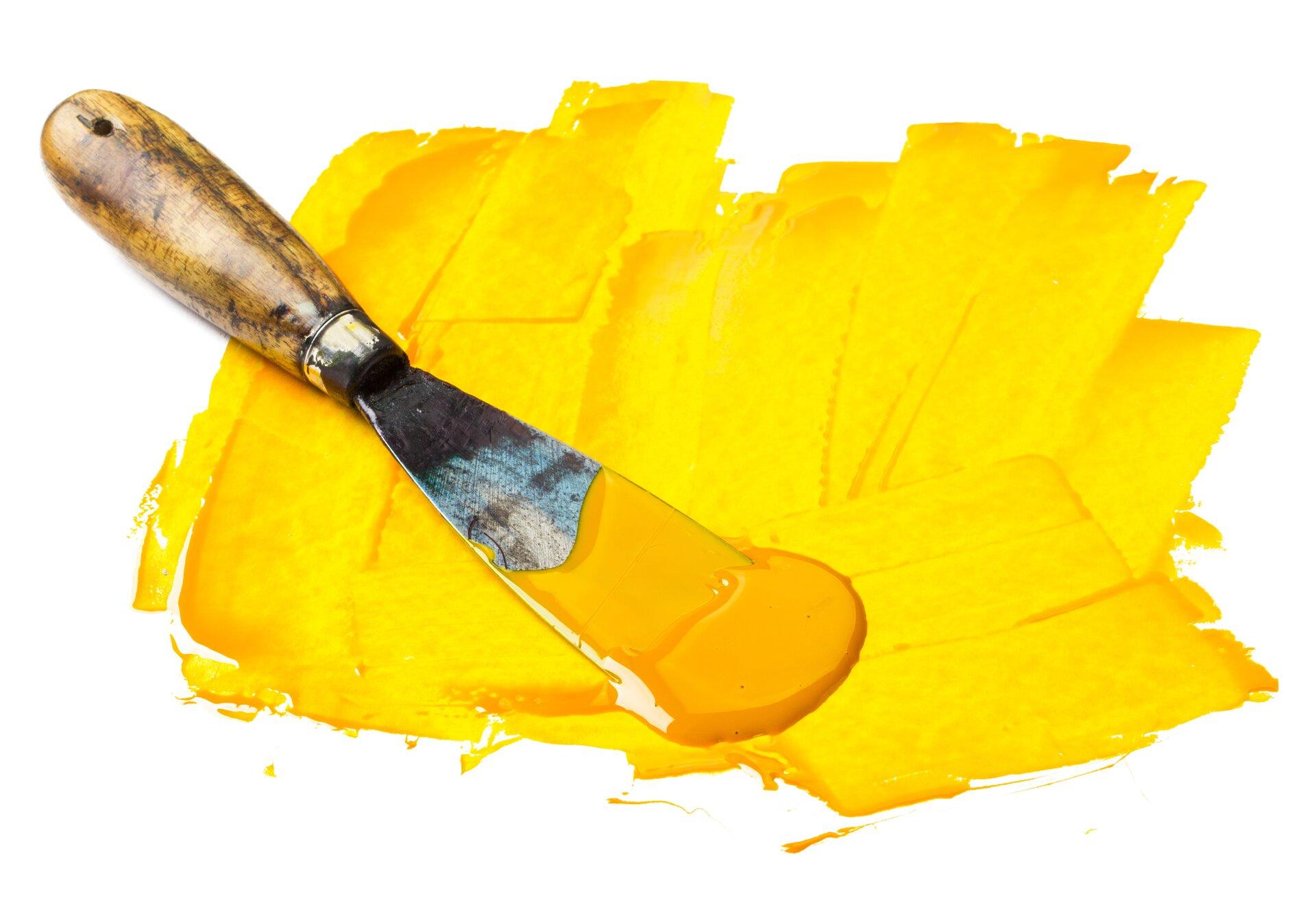 Ilustracja jest fotografią żółtej plamy barwnej,nakładanej szpachlą malarską. Gruba warstwa farby jest nakładana wróżnych kierunkach.