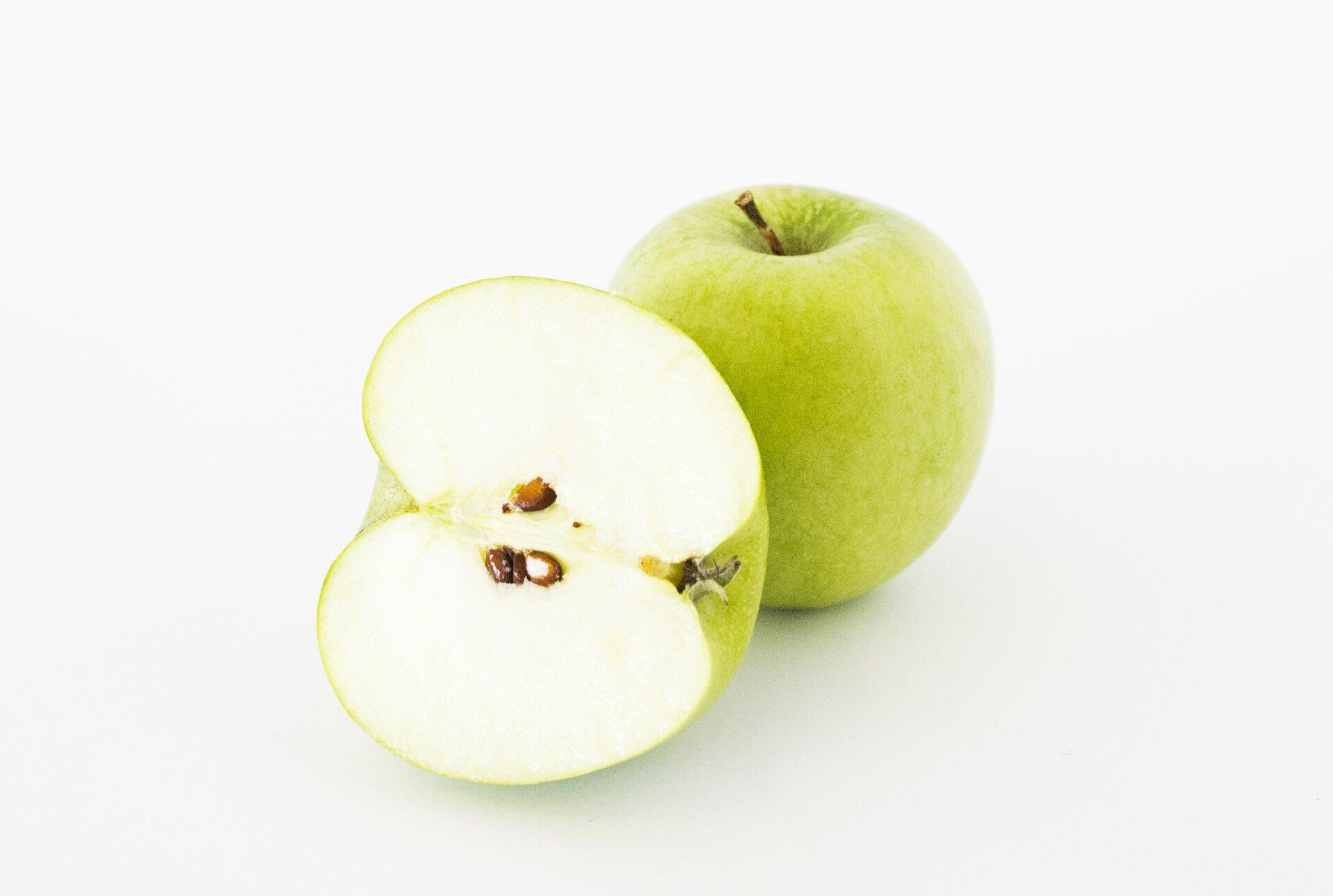 Fotografia jabłek. Jedno jest całe, drugie przekrojone. Na przekroju widać komorę nasienną znasionami.