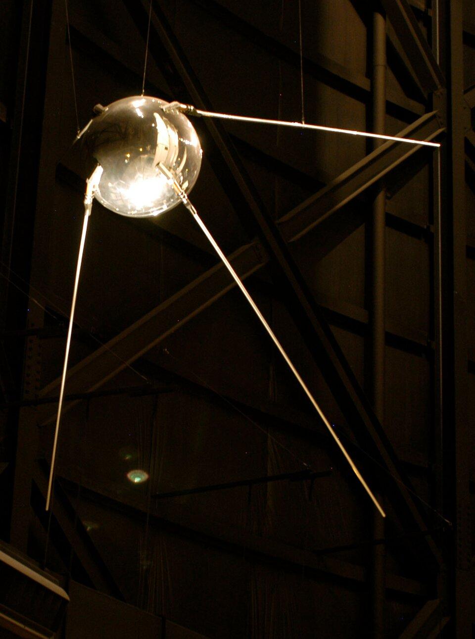 """Zdjęcie przedstawia pierwszego sztucznego satelitę Ziemi – SPUTNIK 1. Tło ciemne, prawie czarne. Na zdjęciu widoczne urządzenie przypominające dużą, srebrną kulę ztrzema cienkimi """"nóżkami"""" odchodzącymi od niej. Powierzchnia błyszcząca."""
