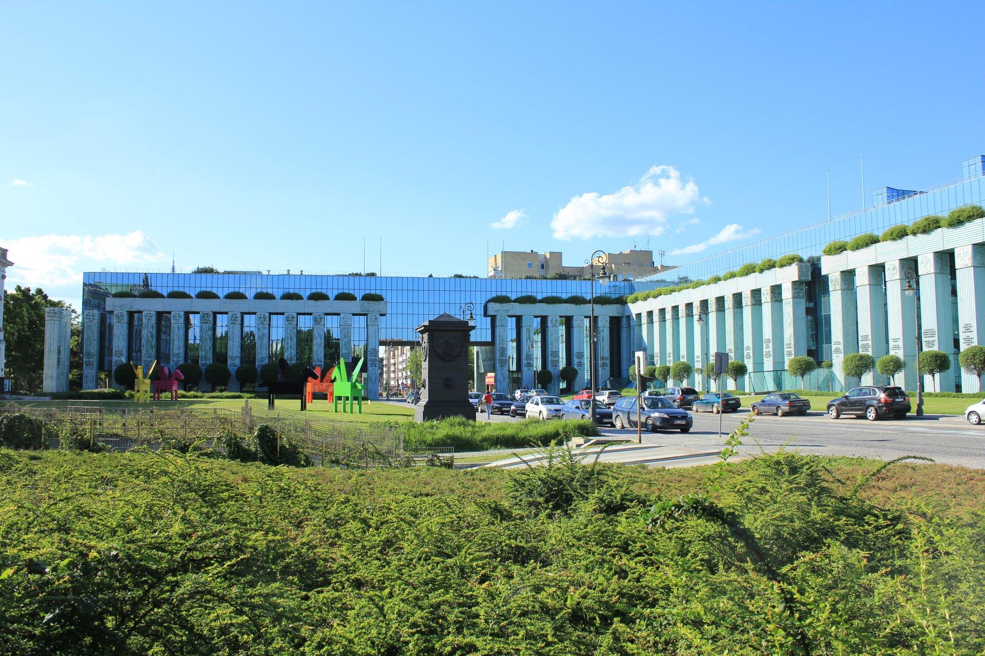 Kolorowe zdjęcie przedstawia budynek Sądu Najwyższego. Widok zprzodu. Po prawej stronie zdjęcia boczne skrzydło budynku. Wgłębi drugie skrzydło budynku, przodem do obserwatora zdjęcia. Budynek kilkupiętrowy ze szkła ibetonu. Wzdłuż fasady budynku wysokie pionowe kolumny zbetonu. Kolumny wkształcie prostopadłościanów. Pomiędzy kolumnami szklana ściana. Kolumny oddalone od siebie co dwa okna. Przed budynkiem duży park. Zielone trawniki. Na środku czarny kamienny pomnik wkształcie prostopadłościanu. Na lewo od pomnika kolorowe rzeźby pegaza. 3 pegazy wkolorach: zielnym, czerwonym, różowym iżółtym. Wzdłuż drogi dojazdowej zaparkowane samochody osobowe