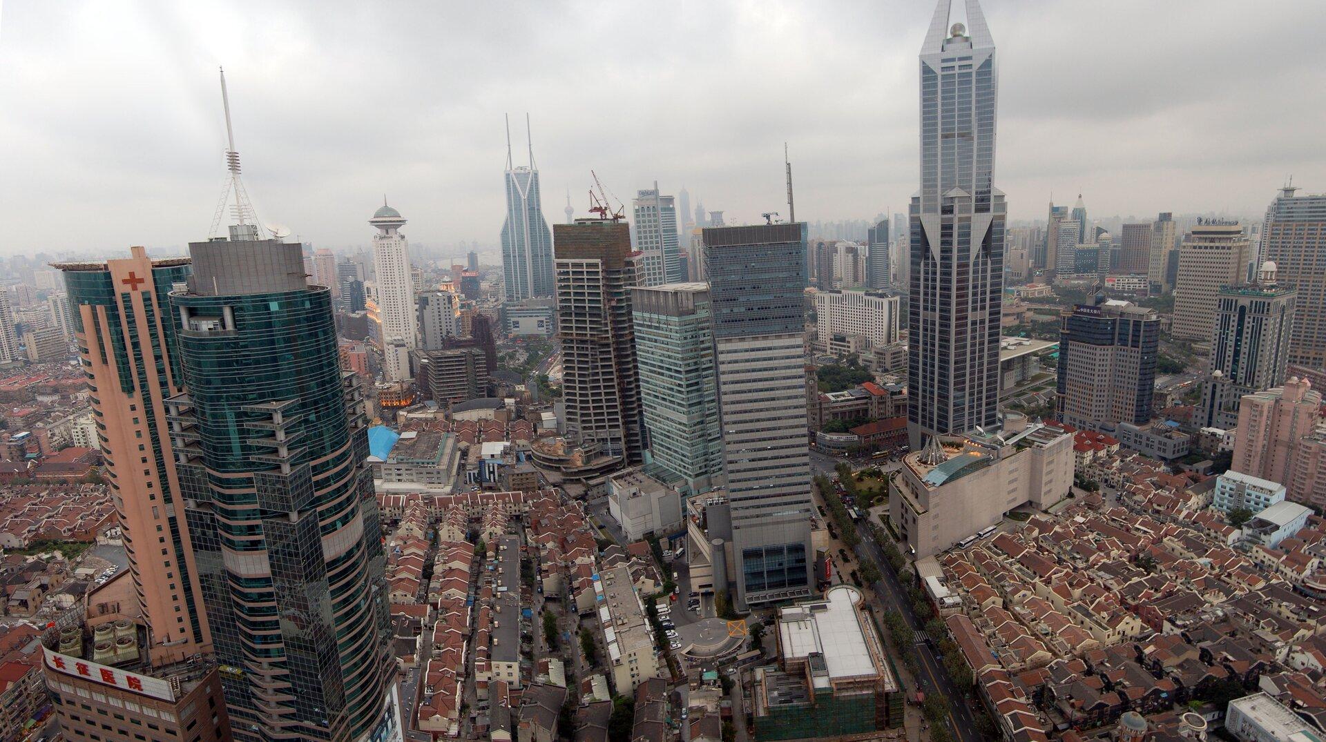 Galeria fotografii prezentująca przykłady krajobrazu silnie przekształconego przez człowieka.Fotografia prezentuje krajobraz miasta zgęstą zabudową, wysokimi budynkami iulicami.