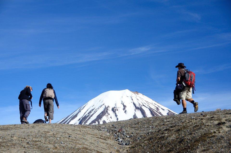 Fotografia prezentuje trzy dorosłe osoby wędrujące szlakiem górskim. Mężczyzna na pierwszym planie ubrany jest wkrótkie spodenki, podkoszulek, kapelusz, buty zgrubą podeszwą. Na plecach niesie plecak. Wtle widoczny ośnieżony szczyt.
