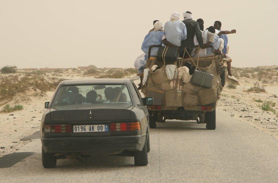 Na zdjęciu dwa samochody (osobowy ipick-up) na drodze wpiaszczystym terenie. Samochody zatłoczone, dużo pasażerów ibagaży.