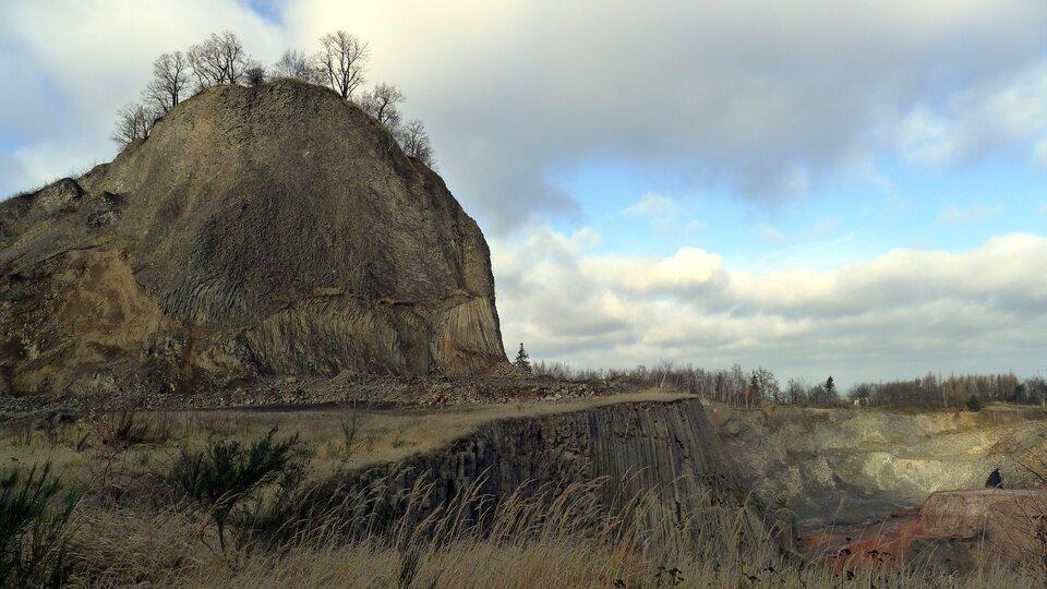 Na zdjęciu skalisty szczyt, strome odsłonięte stoki, wdole wyrobiska.