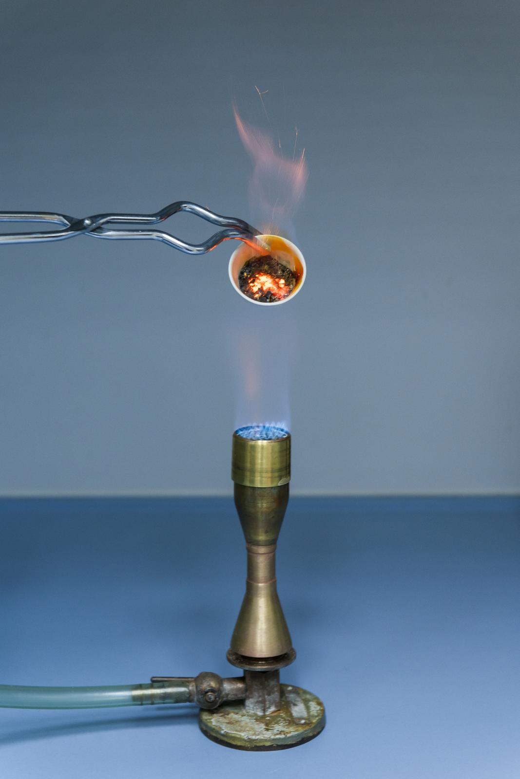 Zdjęcie przedstawia gazowy palnik laboratoryjny, nad którym znajduje się końcówka poziomo ustawionych szczypiec trzymających mały tygielek ogrzewany wpłomieniu iobrócony wlotem wkierunku aparatu. Wtygielku znajduje się rozżarzona mieszanina siarki zżelazem.