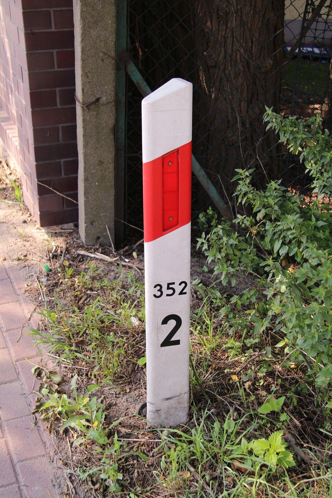 Fotografia przedstawia biało-czerwony słupek przydrożny, na którym umieszczono liczby oznaczające odległości.