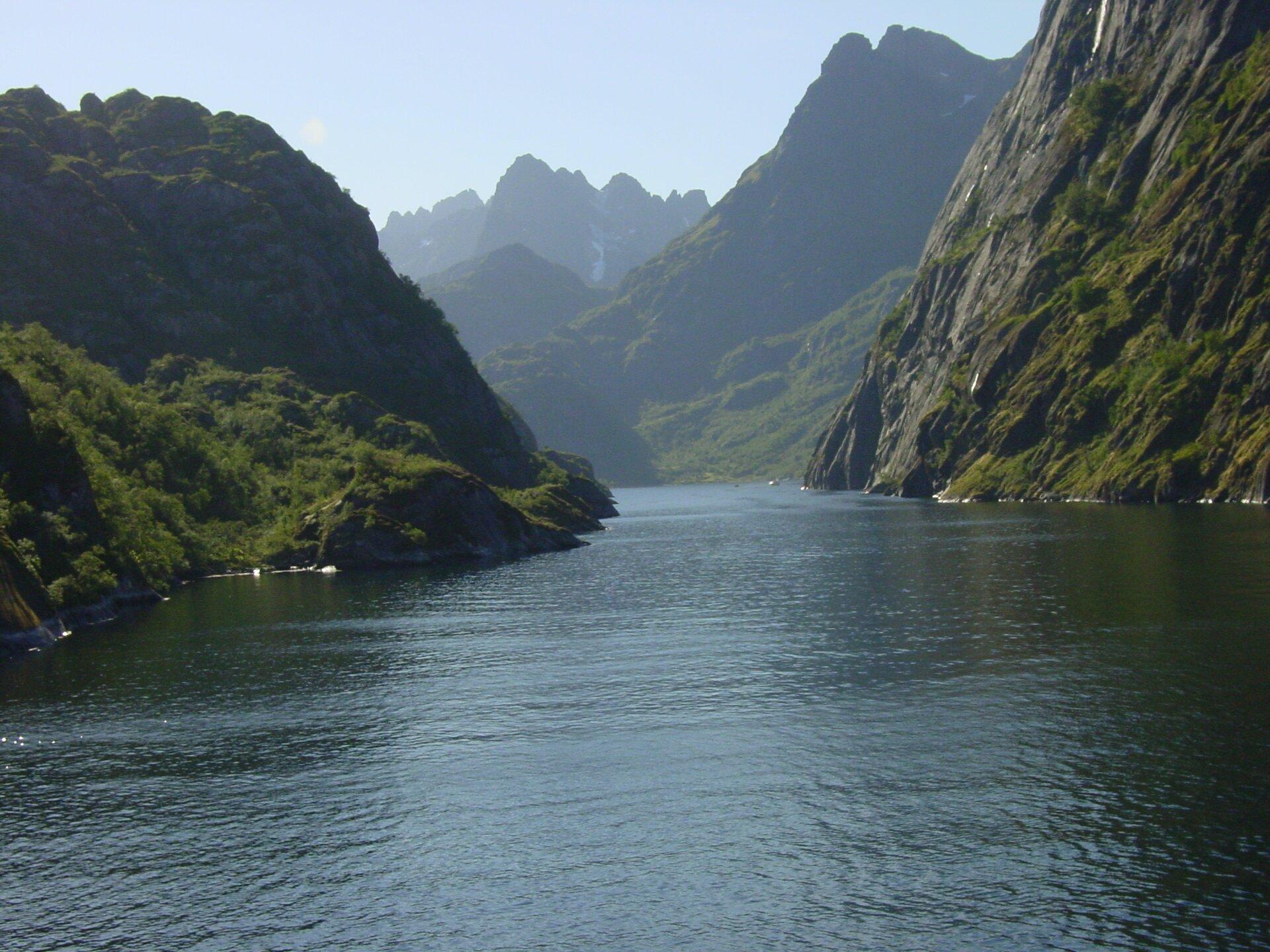 Na zdjęciu wybrzeże fiordowe. Długa wąska zatoka ostromych brzegach. Wtle wysokie góry. Stoki porośnięte roślinnością.