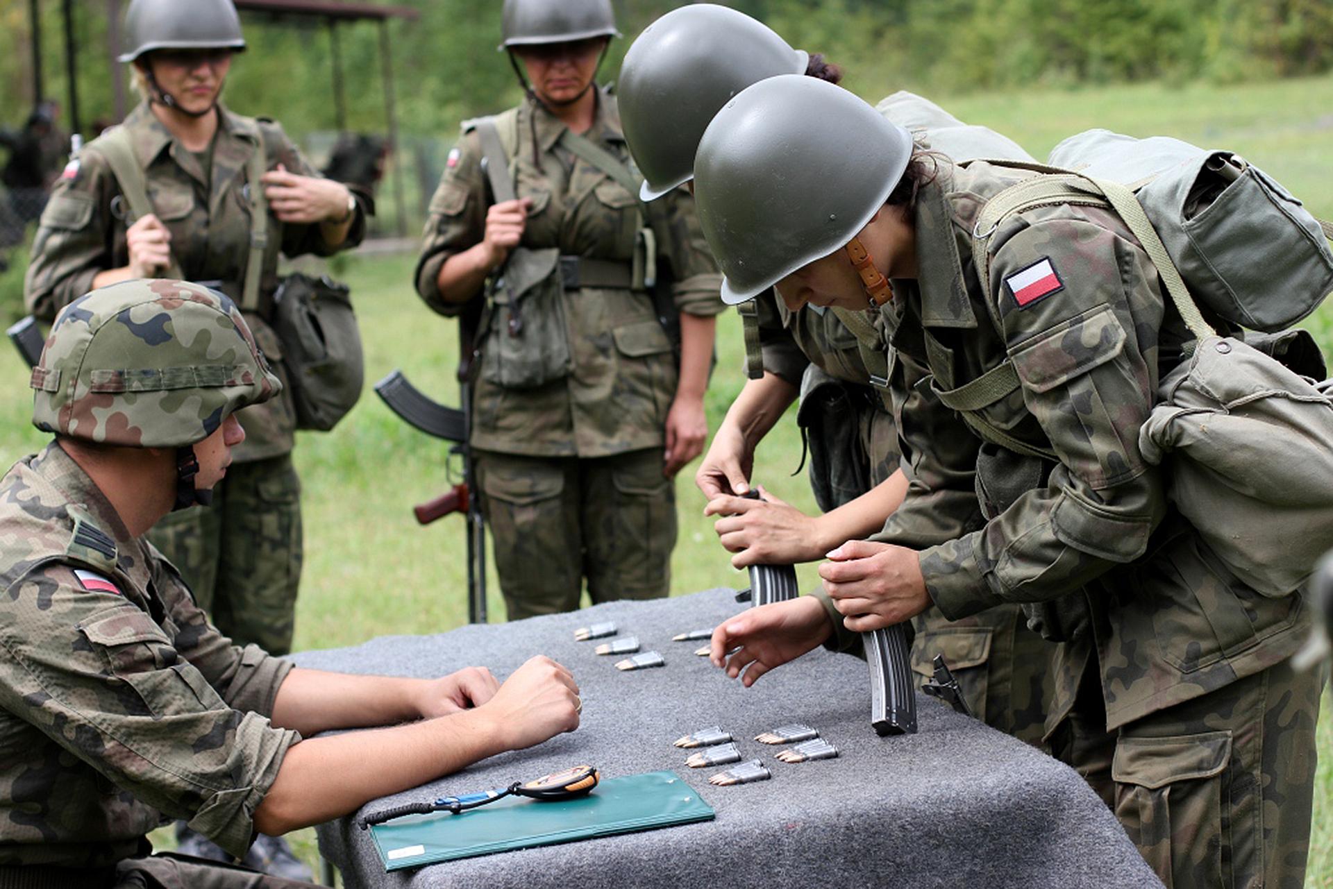 Kolorowe zdjęcie przedstawia grupę żołnierzy wtrakcie szkolenia. Na pierwszym planie mieści się stół nakryty materiałem. Po lewej stronie stołu siedzi żołnierz, zaś po prawej stronie stoją dwaj żołnierze. To kobiety. Kobiety składają karabin zelementów ułożonych na stole. Wgłębi zdjęcia 2 żołnierze przodem do obserwatora. Wszystkie osoby ubrane wmundury wodcieniach ciemnej zieleni. Na głowach kaski, na plecach plecaki. Wgłębi zdjęcia zielona polana ilas.