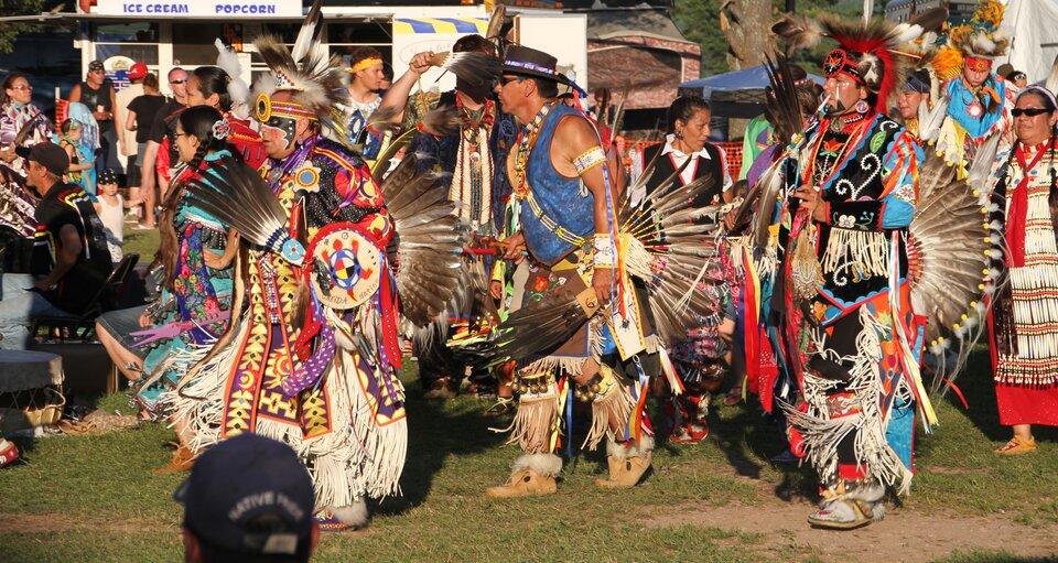 Na zdjęciu Indianie wkolorowych strojach ozdobionych piórami.