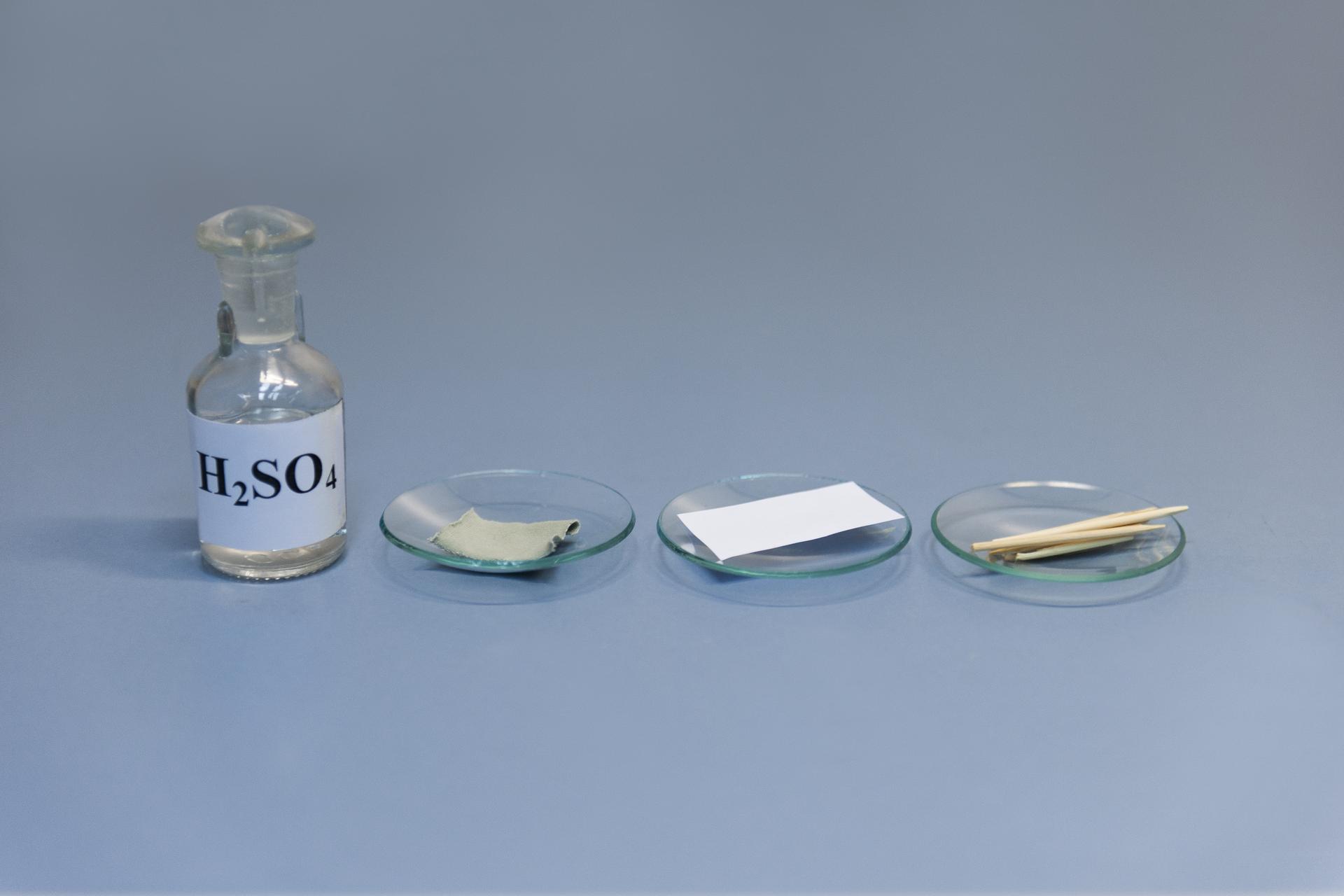 Pierwsze zdjęcie wgalerii. Na ilustracji prezentowana jest szklana butelka zetykietką inapisem H2SO4 stojąca na niebieskim podłożu. Po jej prawej stronie na blacie laboratoryjnym stoją wszeregu trzy szkiełka zegarkowe zawierające kolejno: kawałek tkaniny, kawałek papieru ikilka drewnianych połówek wykałaczek.