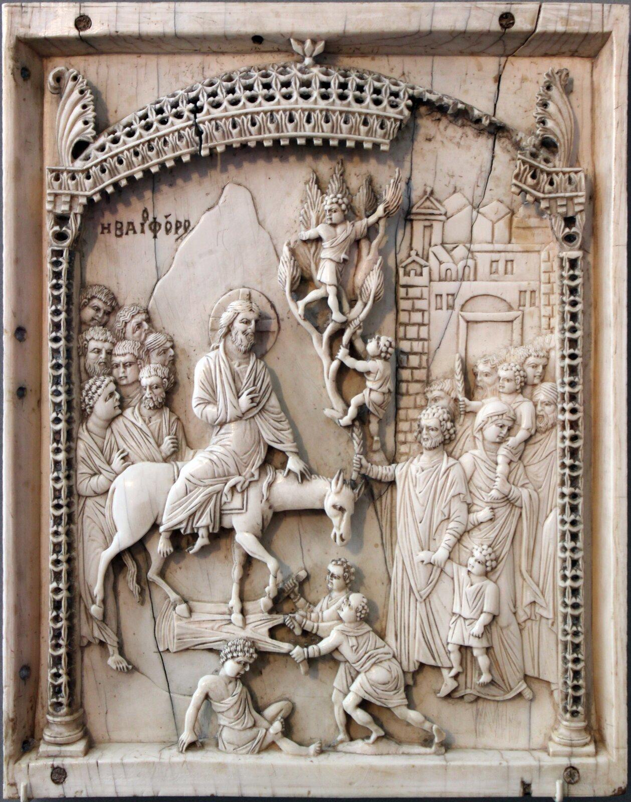"""Ilustracja przedstawia płaskorzeźbę nieznanego autorstwa pt. """"Wjazd Chrystusa do Jerozolimy"""". Na tej rzeźbie przedstawiona została scena, wktórej Chrystus wjeżdża do miasta Jerozolima. Jezus jest witany przez tłum ludzi."""