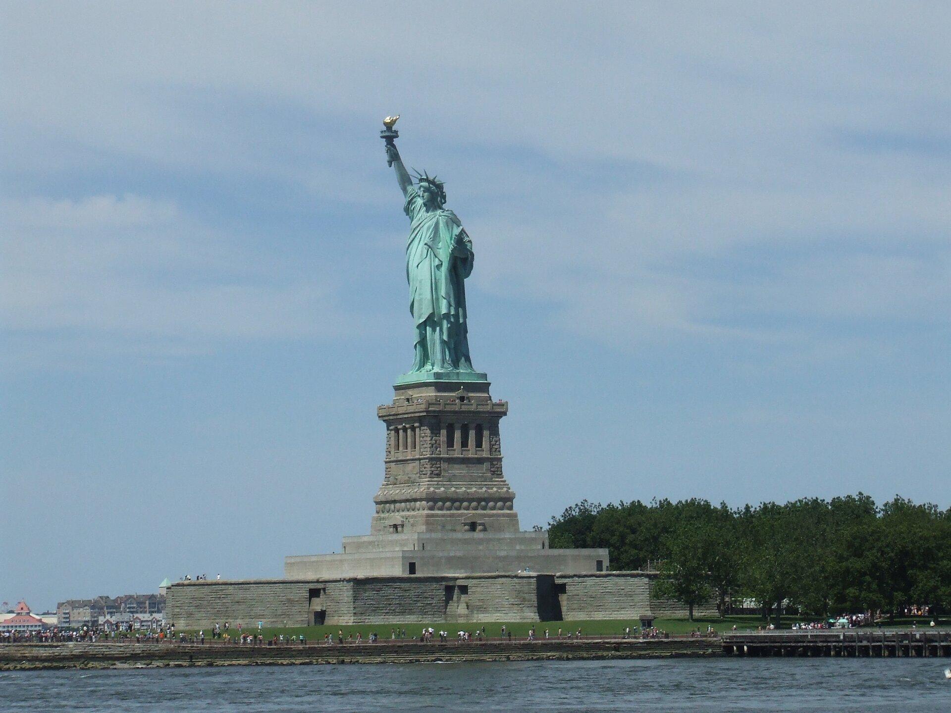 Na zdjęciu pomnik postaci kobiecej zuniesioną ręką trzymająca pochodnię. Stoi na wysokim kamiennym postumencie. Dookoła ludzie. Na pierwszym planie woda.